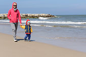 Mother walks on a beach with her litlle son