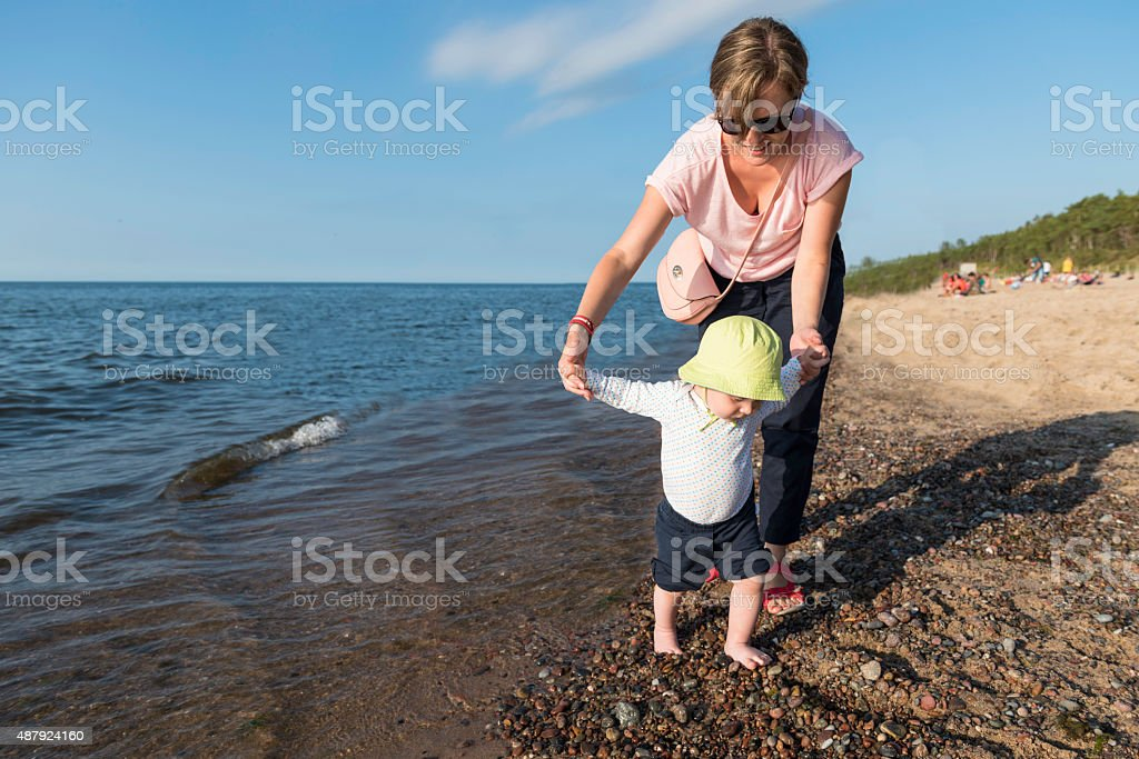 Mother walks with her child along beach stock photo