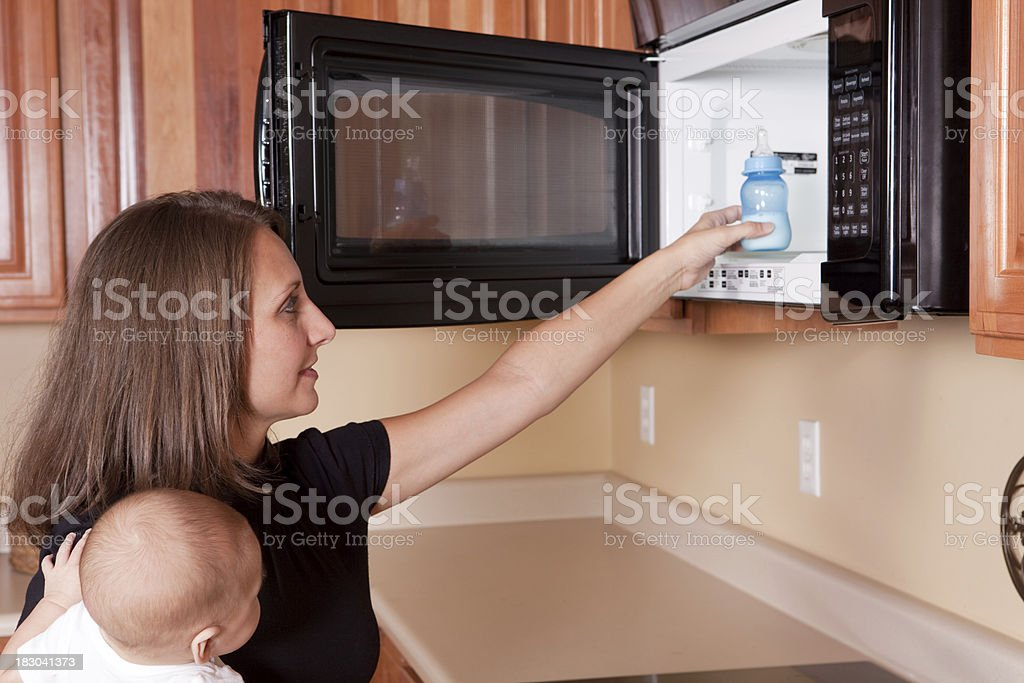 Mother Warming Baby Bottle In Microwave stock photo