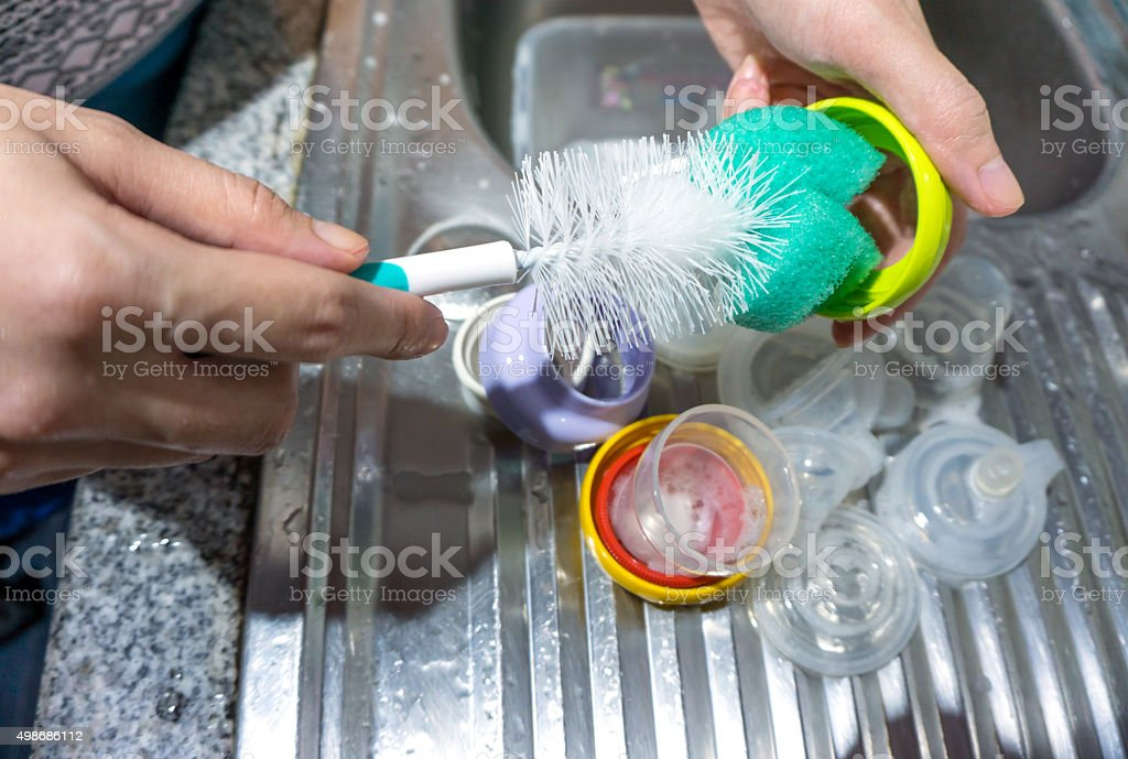 Mother washing baby milk bottle stock photo