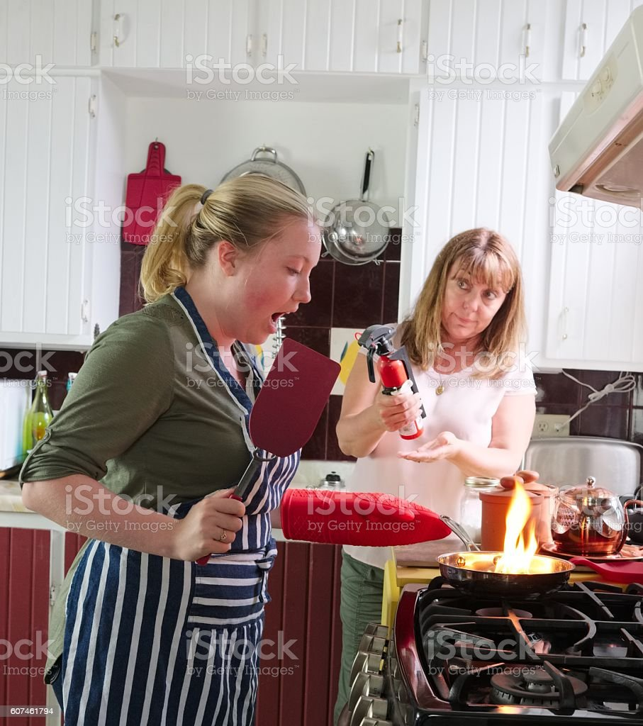 Mother watches as daughter burns dinner, flaming frying pan. stock photo