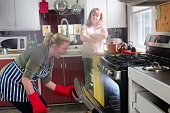 Mother watches as daughter burns dinner, smoke from oven.