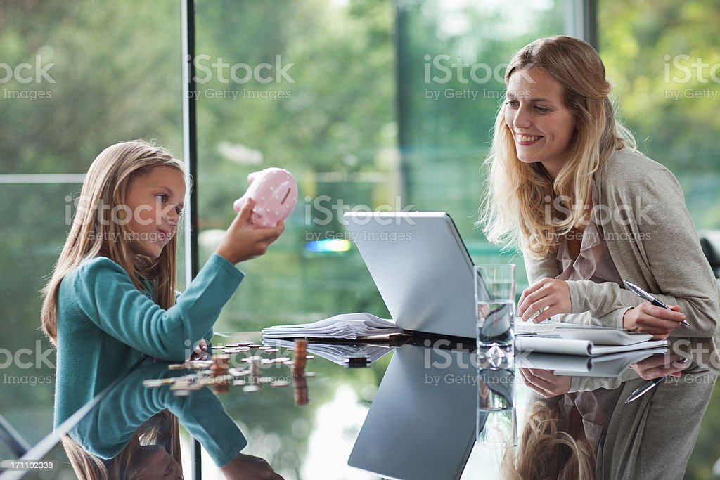 Mother watching daughter count coins from piggy bank stock photo