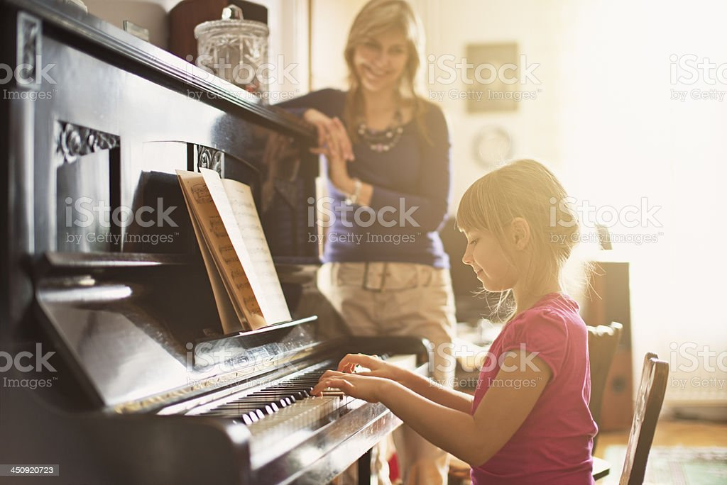 Mother watching daughter that is playing piano stock photo