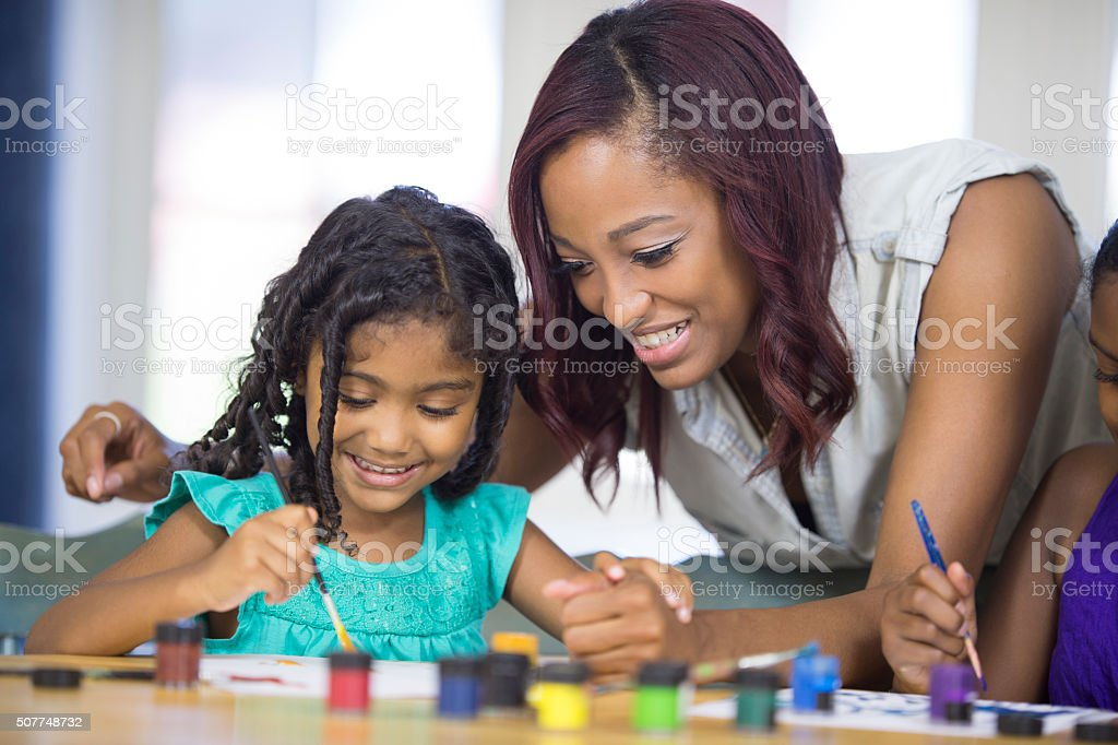 Mother Watching Her Daughters Paint Together stock photo