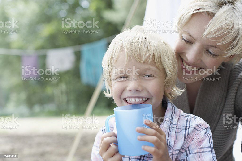 Mother watching son drinking at campsite royalty-free stock photo