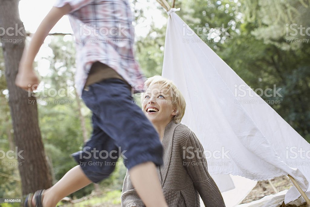 Mother watching son play in woods royalty-free stock photo