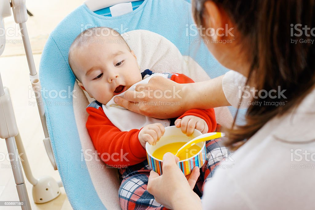 Mother wipes baby's mouth stock photo