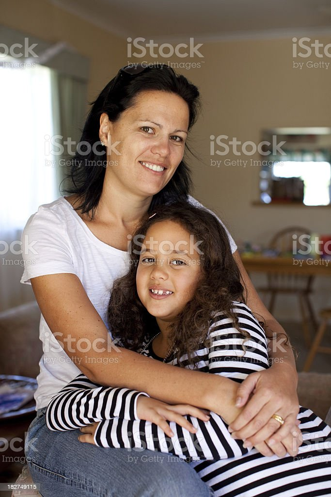 Mother with arms around her daughter indoors stock photo