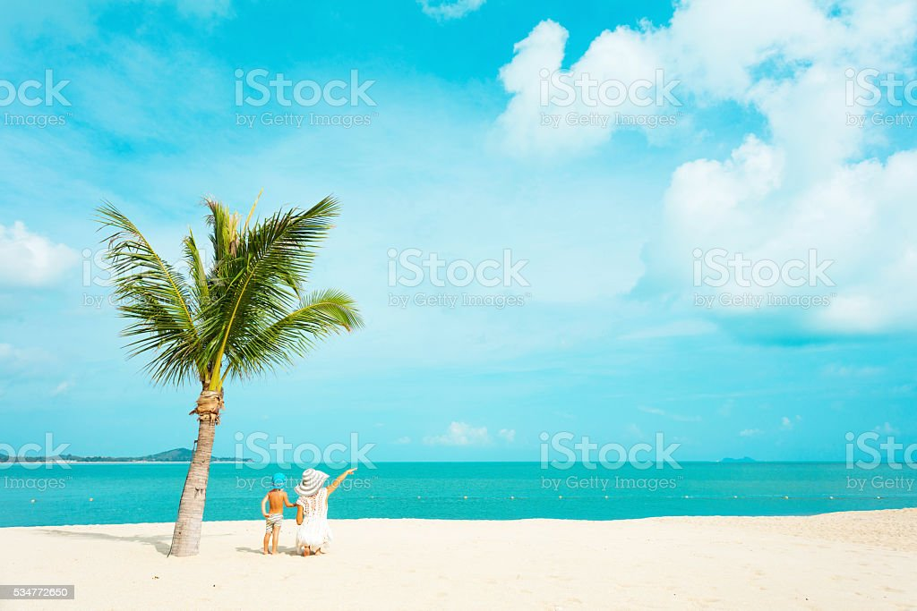 Mother with baby at tropical beach stock photo