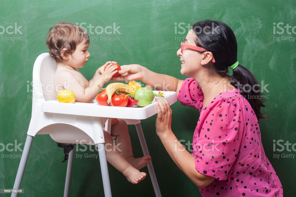 Mother With Baby Boy Eating On High Chair In Front Of Green Chalkboard stock photo
