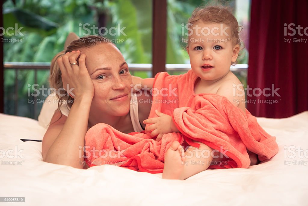 Mother with baby daughter relaxing on bed in home interior stock photo
