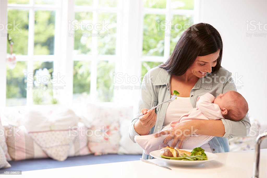 Mother With Baby Eating Healthy Meal In Kitchen stock photo