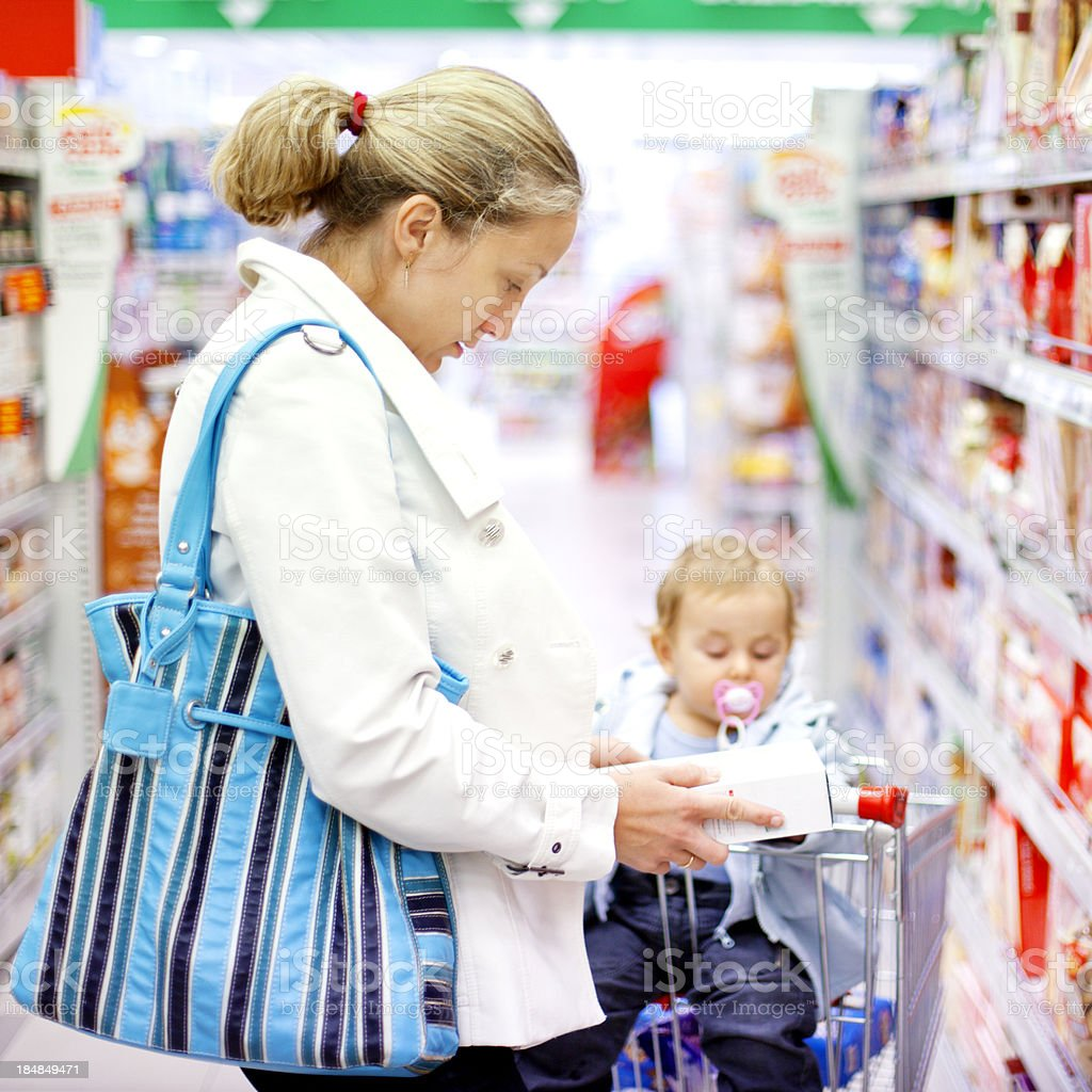 Mother with baby girl shopping in the supermarket royalty-free stock photo