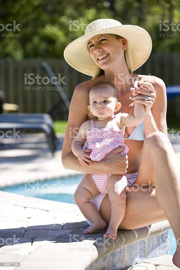 Madre con bebé niña sala de estar junto a la piscina por vacaciones foto de stock libre de derechos