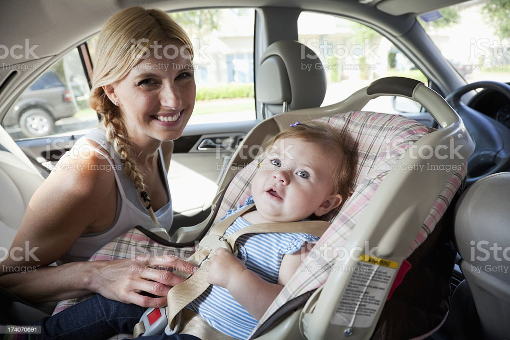 Mother with baby in car seat stock photo