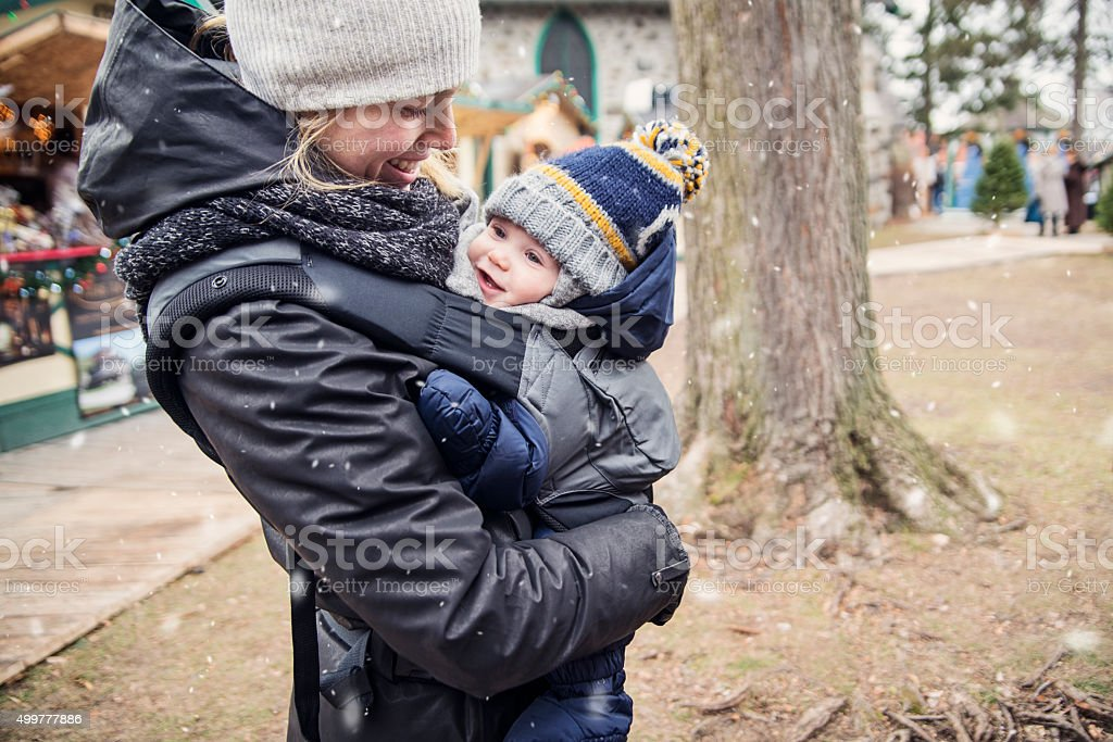 Mother with baby in carrier enjoying first snow public park. stock photo