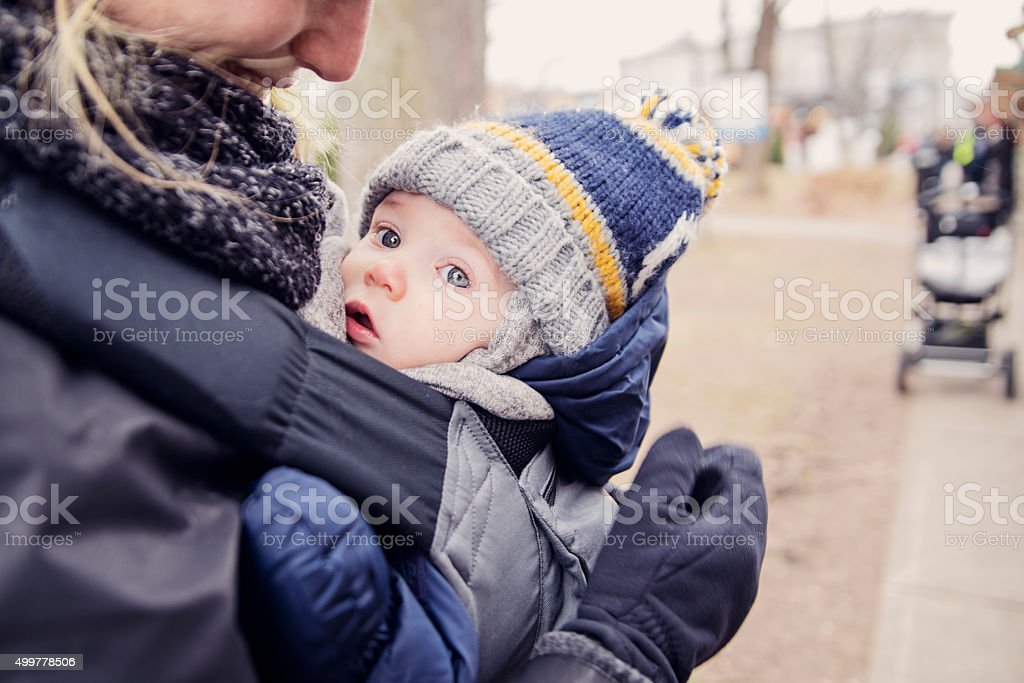 Mother with baby in carrier, outdoors in winter. stock photo