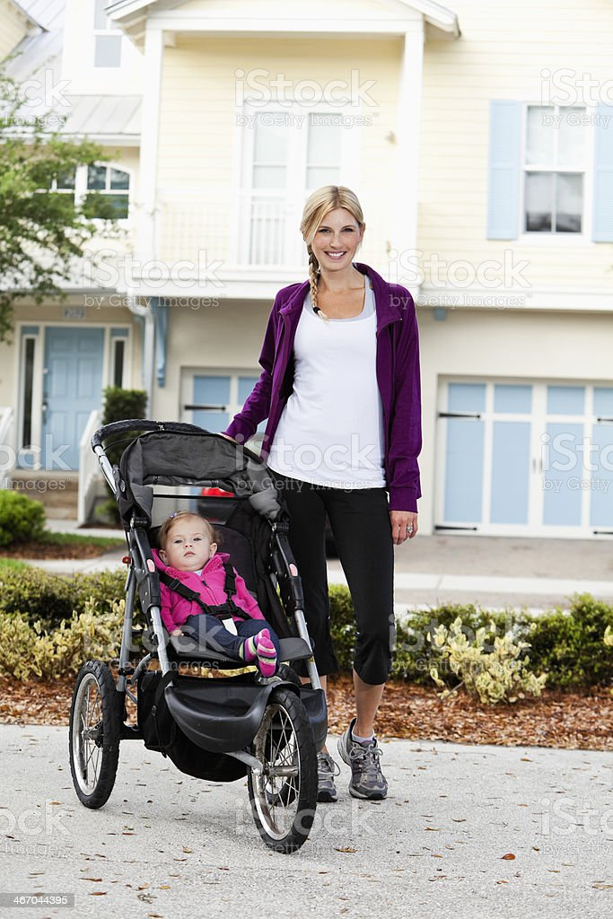 Mother with baby in jogging stroller stock photo