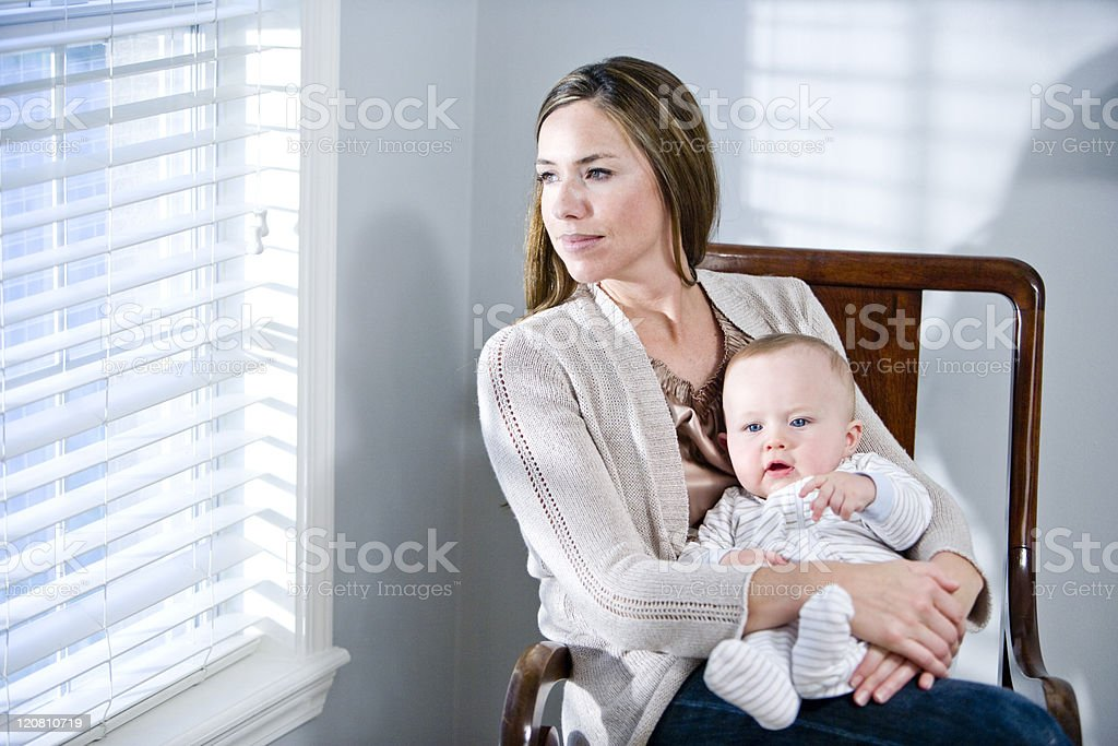 Mother with baby in lap sitting by window royalty-free stock photo