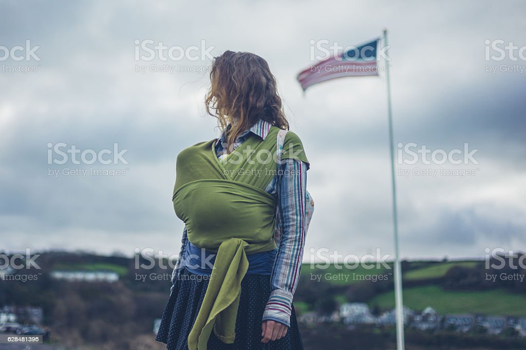 Mother with baby in sling under american flag stock photo