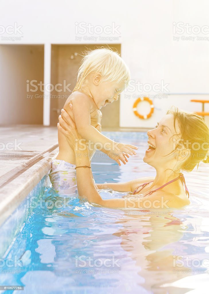 Mother with baby in the swimming pool stock photo