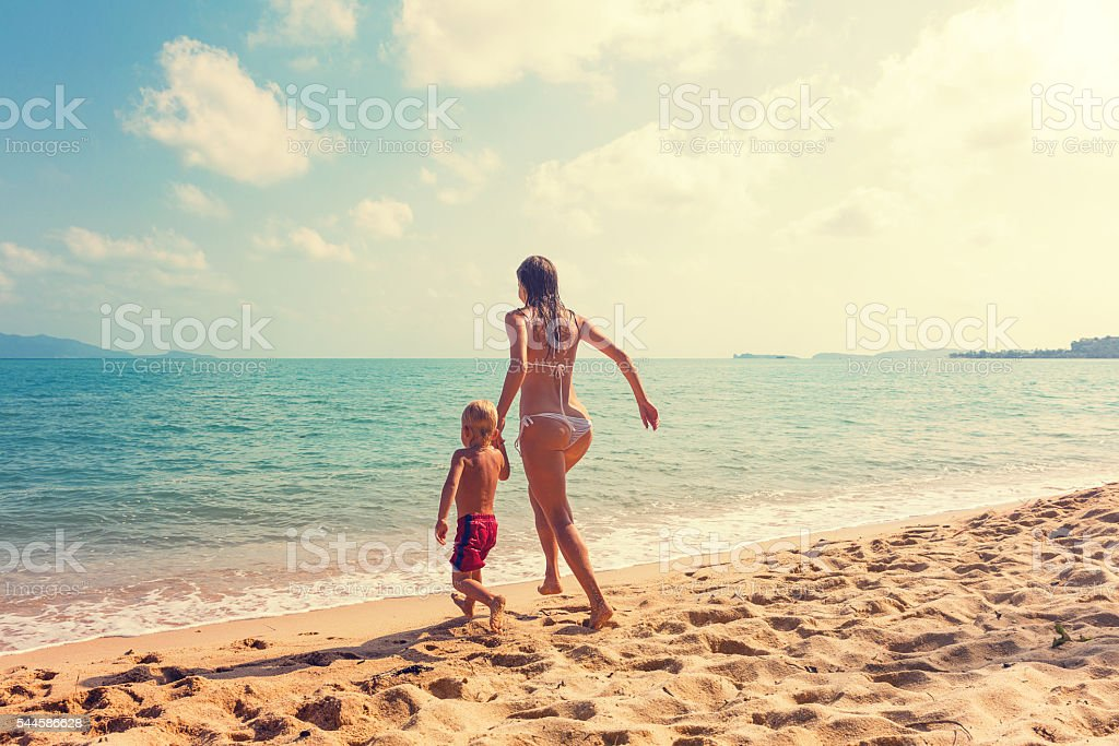 Mother with baby runnig at tropical beach stock photo