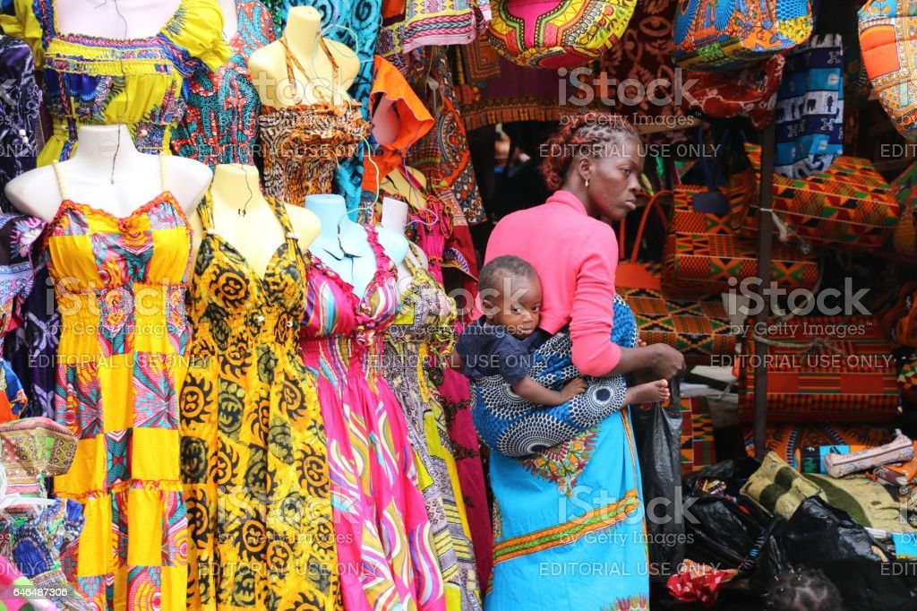 Mother with Baby sells Traditional African Textiles Stall, Lomé, Togo, West Africa stock photo