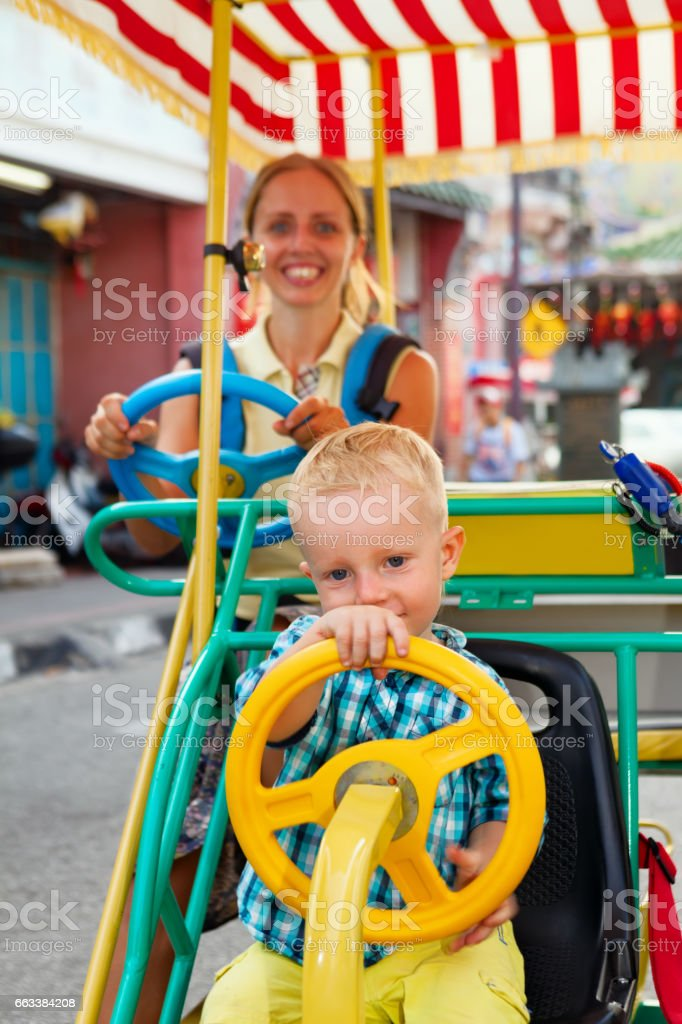 Mother with baby son have fun, riding on rental quadricycle stock photo