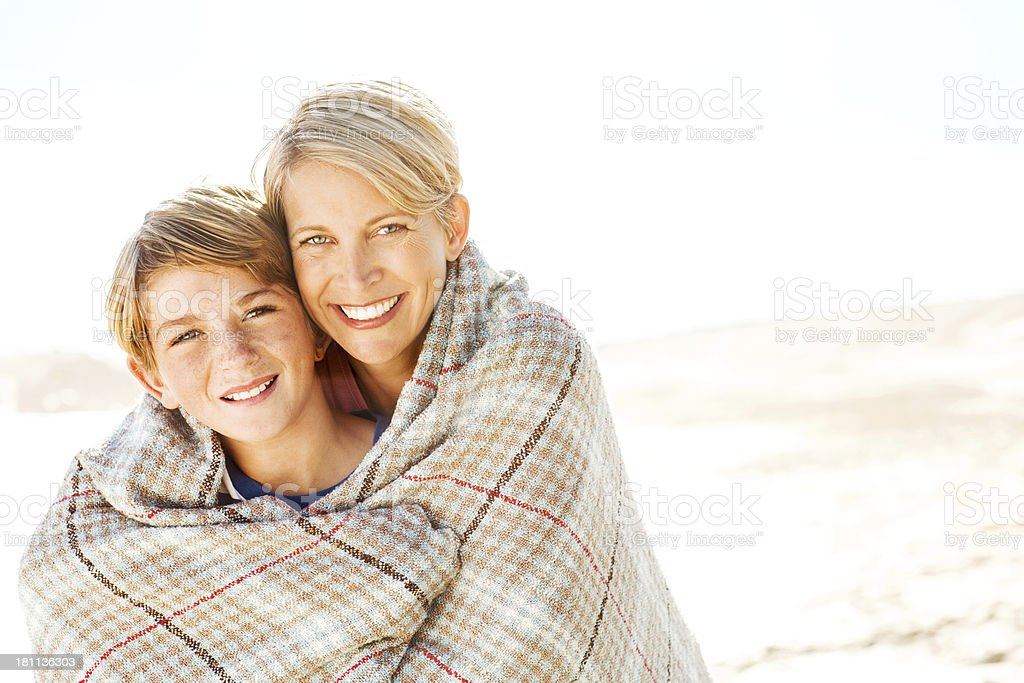 Mother With Blanket Embracing Son From Behind At Beach royalty-free stock photo