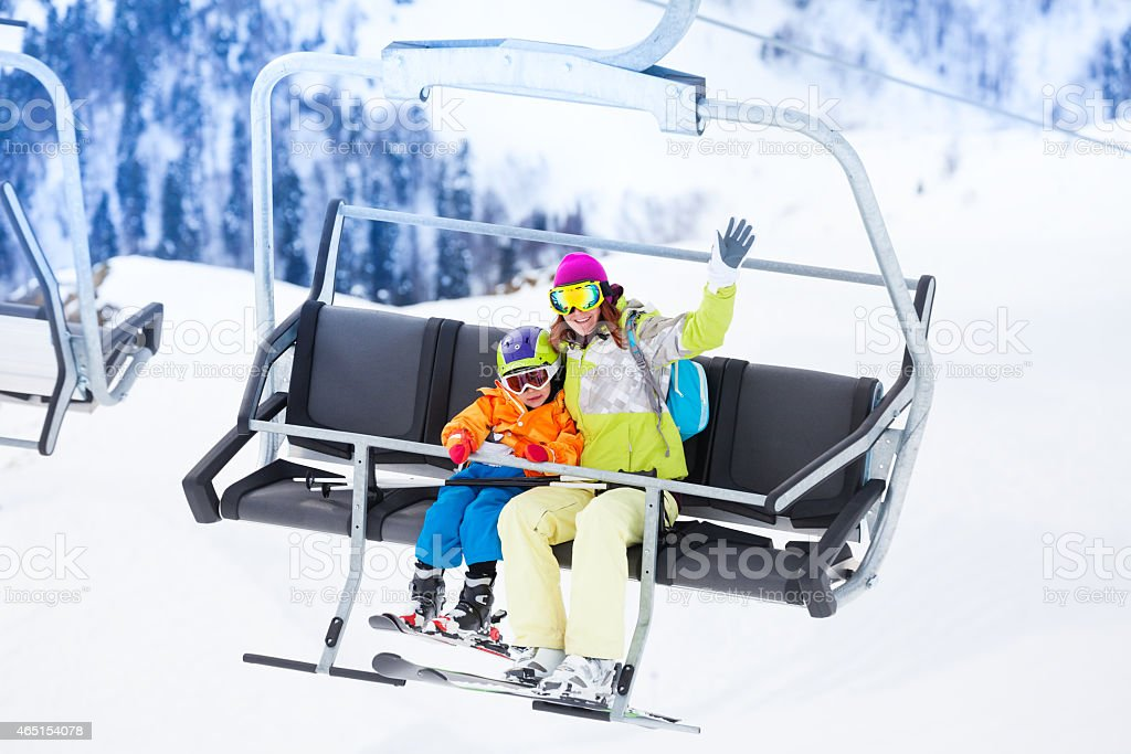 Mother with boy lifting on ski lift stock photo