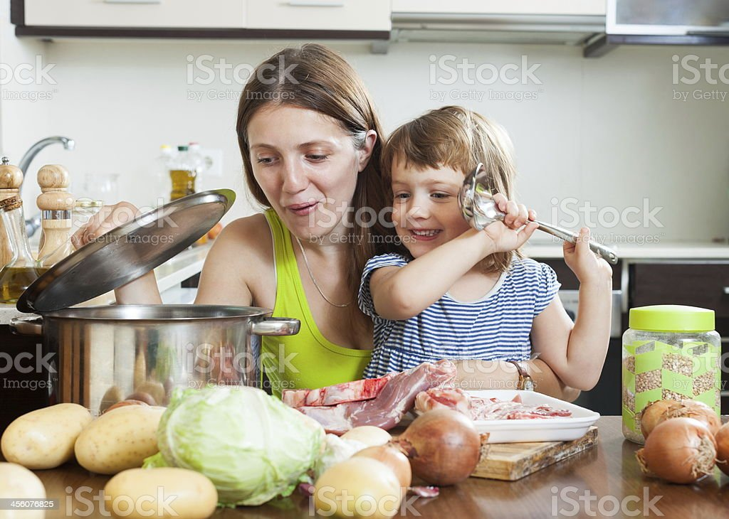 Mother with child making soup stock photo