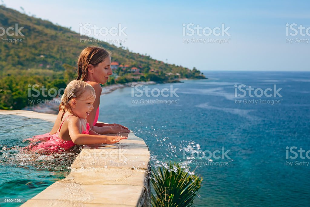Mother with child swim with fun in infinity pool stock photo