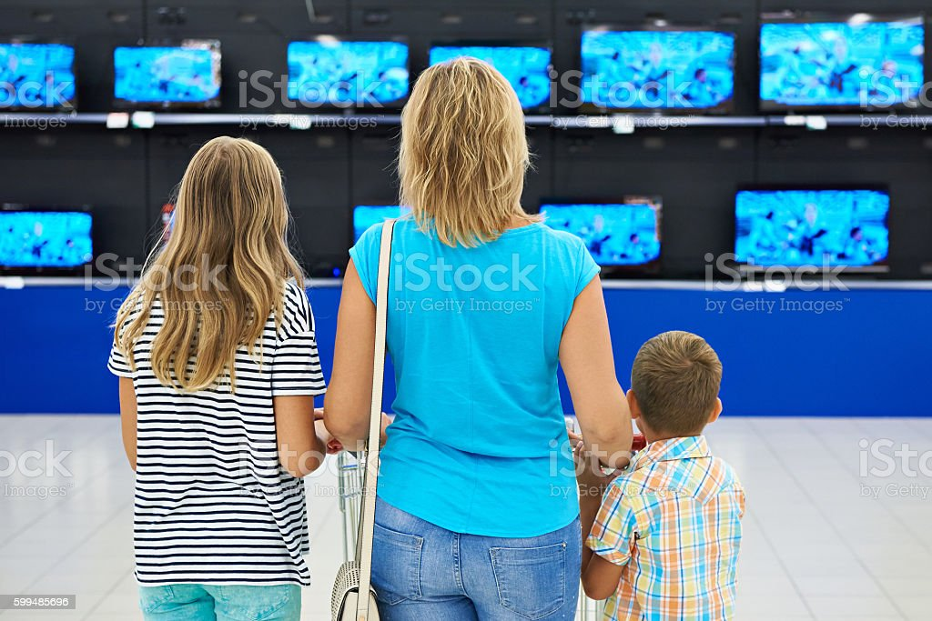 Mother with children in shop of tv stock photo