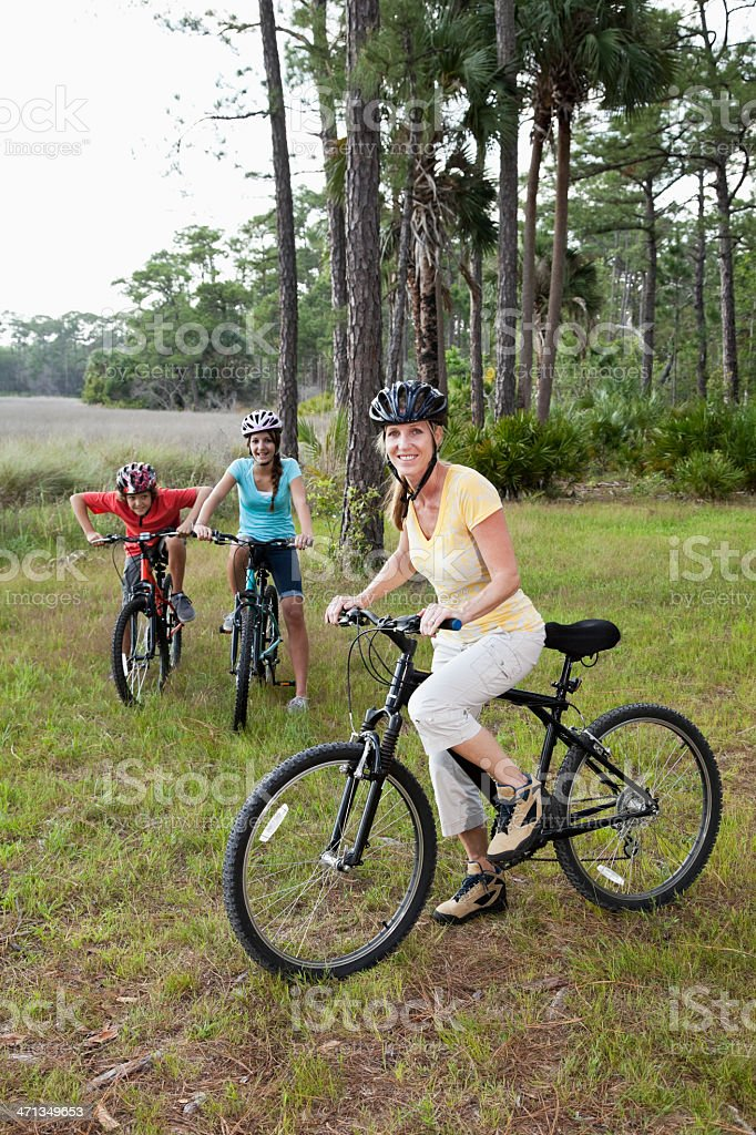 Mother with children riding bicycles stock photo