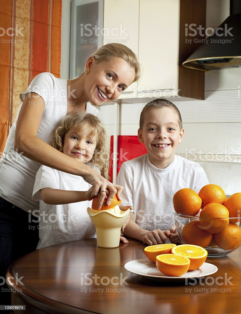 Mother with children squeezed orange juice royalty-free stock photo