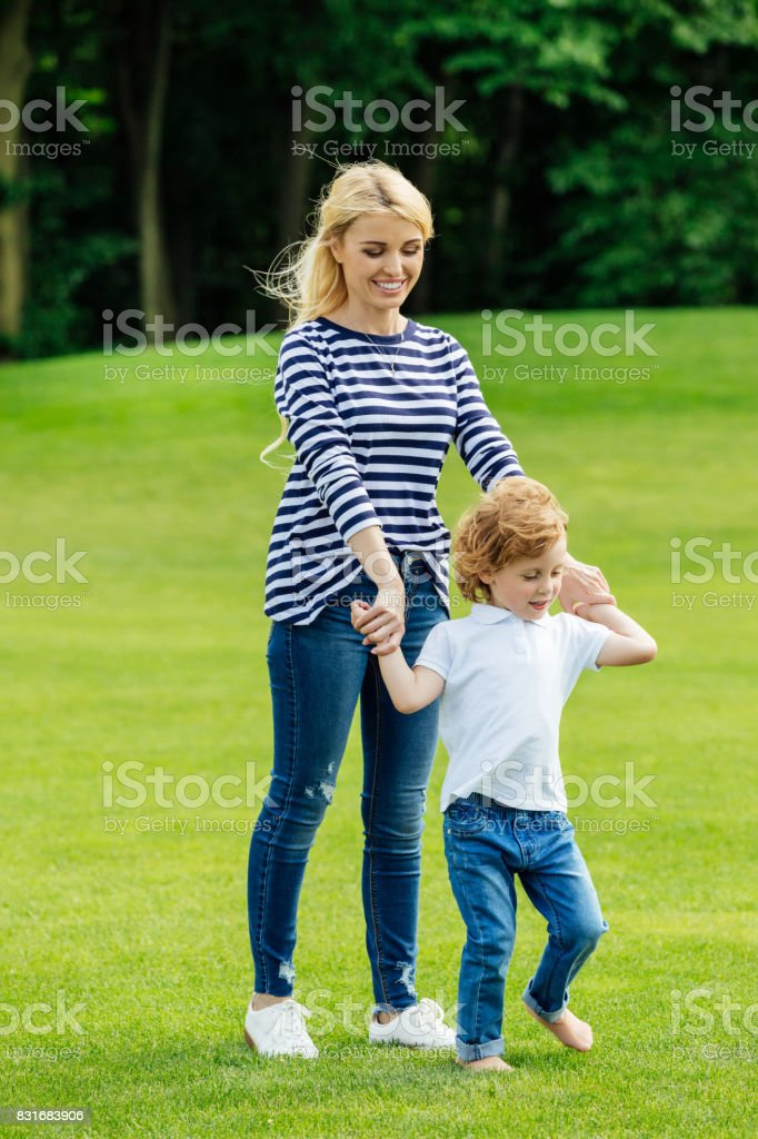 mother with cute little son holding hands while walking on green lawn in park stock photo