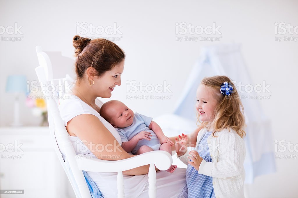 Mother with daughter and baby in a white nursery stock photo