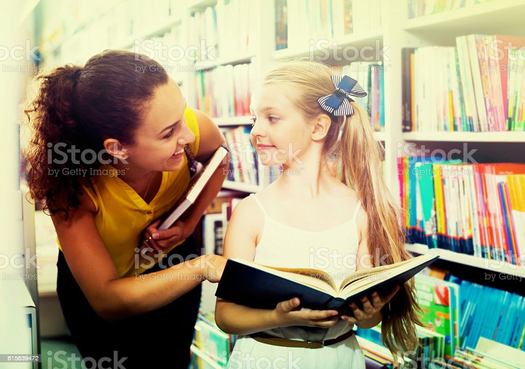 Mother with daughter in bookstore stock photo