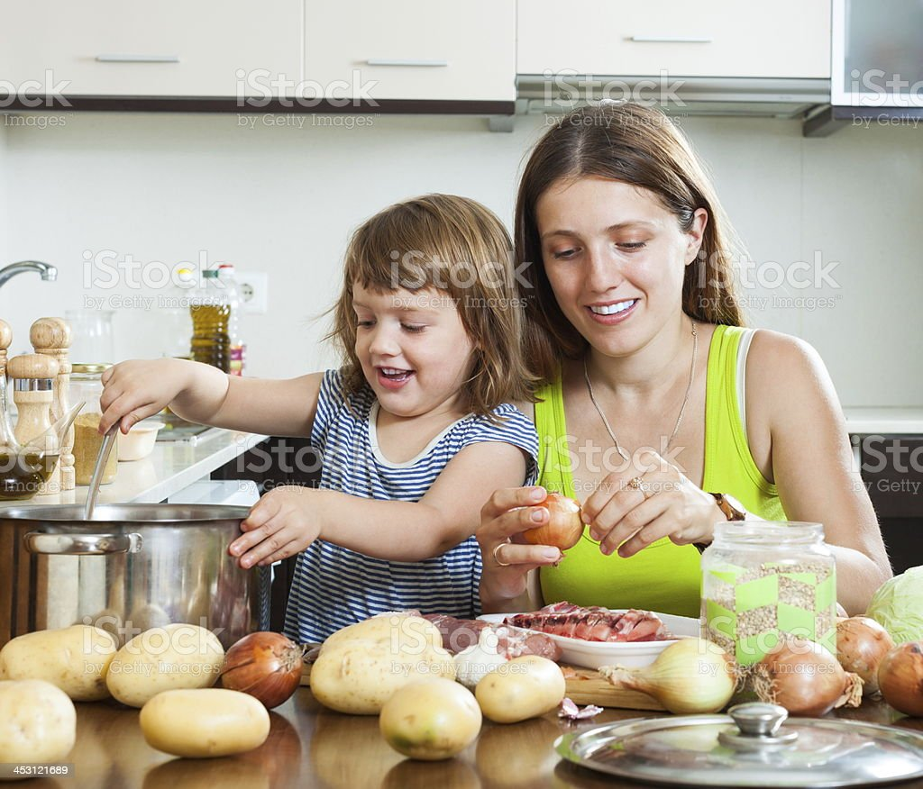 Mother with daughter making soup stock photo