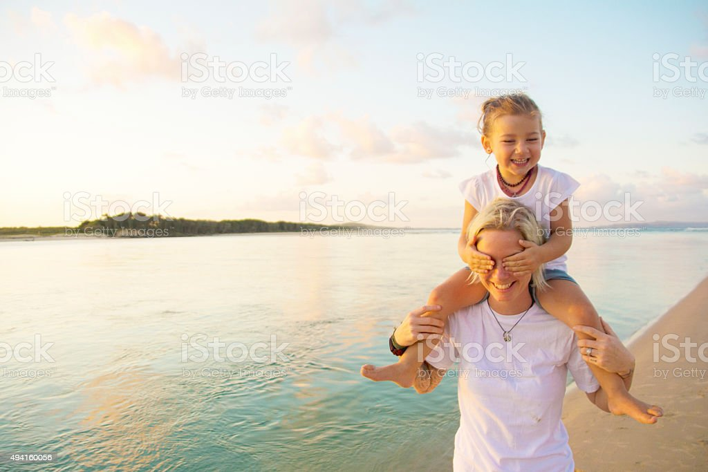Mother with daughter on her shoulders stock photo