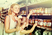 Mother with daughter shopping conserve crushed tomatoes