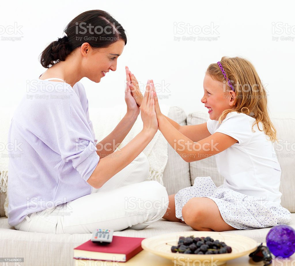 Mother with daughter sitting on sofa and playing clapping game stock photo