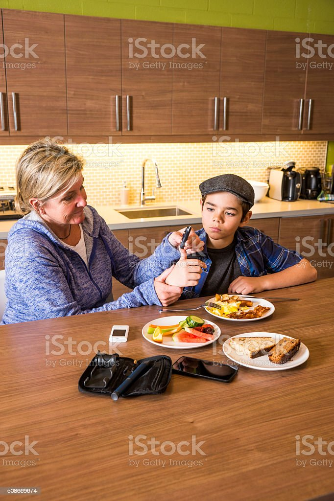 Mother with diabetic son at home in the kitchen stock photo