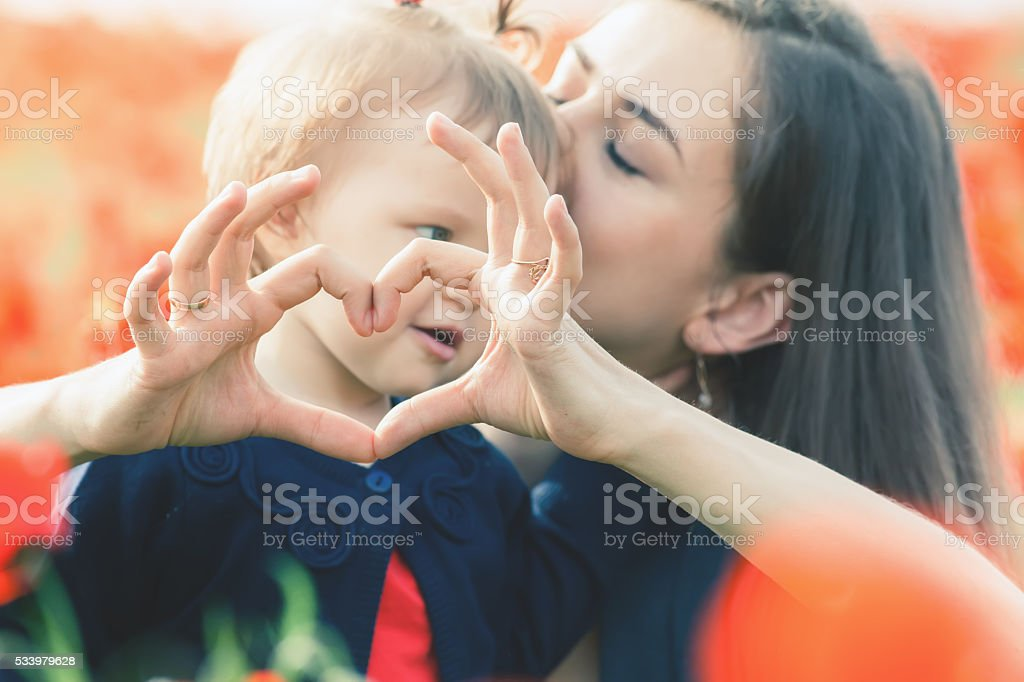 Mother with funny child outdoor at poppy flowers field stock photo