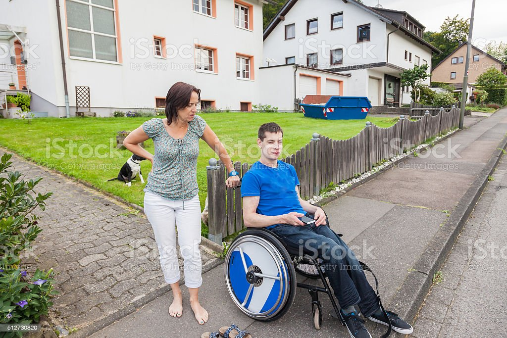 Mother with handicapped son waiting for the school bus stock photo