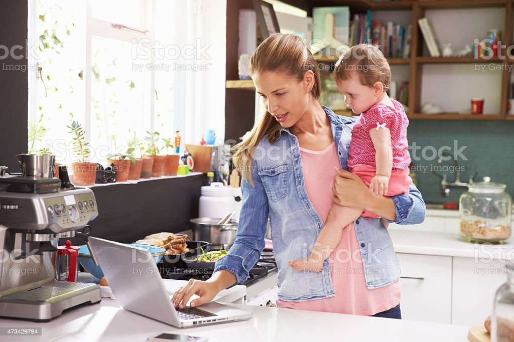 Mother with her baby using a laptop in the kitchen stock photo