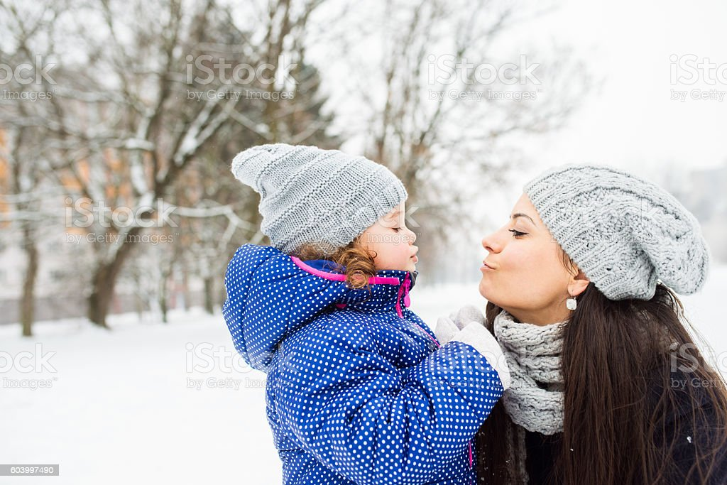Mother with her daughter kissing outside in winter nature stock photo