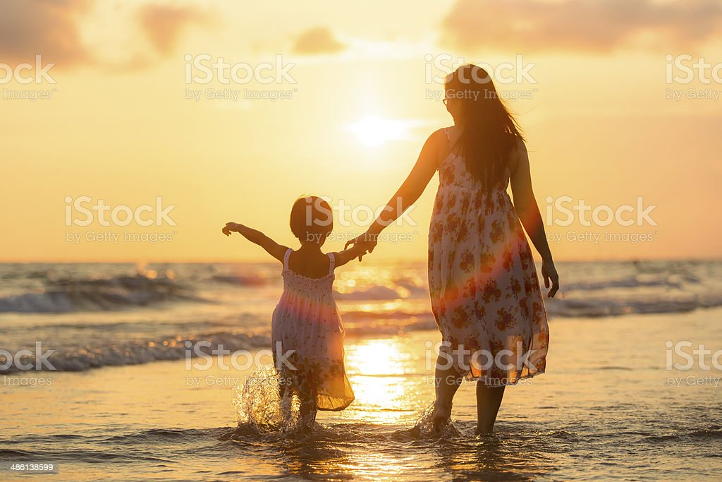 Mother with her daughter on the beach stock photo