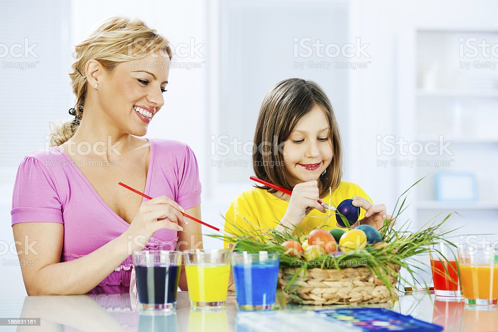 Mother with her daughter painting Easter eggs. royalty-free stock photo